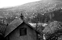 BOSNIA-HERZEGOVINA, Belgrade-Sarajevo Road, 03/2003..The bus overhangs Sarajevo, his white muslim cemeteries and the minarets of the mosques. 200000 persons died during the war between 1992 and 1995.  .BOSNIE-HERZEGONVINE, Route Belgrade-Sarajevo, 03/2003..Photo prise depuis le bus qui relie Belgrade à Sarajevo. Le bus surplombe Sarajevo, son cimetière musulman blanc et les minarets des mosquées. 200000 personnes sont mortes pendant le siège de la ville entre 1992 et 1995..© Bruno Cogez / Est&Ost Photography