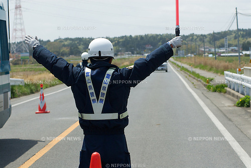 MAY 4, 2011- A police officer halts a car as it leaves the Fukushima exculsion zone at a check point at the border of the exclusion zone in Minami Soma, Fukushima, Japan. The officers all from Tohoku have been on duty for a month and will return home today. A 9.0 Earthquake and Tsunami damaged the Fukushima Daiichi Nuclear power causing a nuclear accident that was upgraded to a level 7 nuclear accident. Residents within the 20km exclusion zone have evacuated those within the 20-30 km zone have been told to stay indoors. (Photo by B.Meyer-Kenny/2.0 Images)