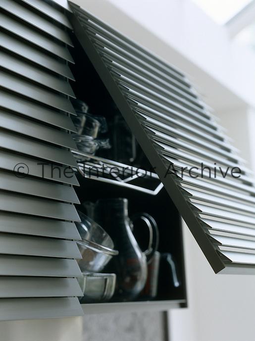 Aluminium louvered upward-opening cupboard doors reveal shelves of glassware