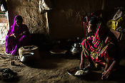 25 year old Sri Kanthi Devi sits down to eat her lunch while her son its carried by her sister in law, Lal Chuni Devi in their kitchen in Ramgarwa village in Raxaul district in Bihar, India.