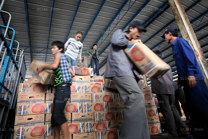 Vietnamese day laborers load a truck with boxes of melons from China's far western Xingjiang region to be sold in vietnam at a truck stop and de facto trading center in the border town of Puzhai, Guangxi Province, China on 06 July 2009.  Cross border trade between the two countries has skyrocketed in the past decade, and China is currently planning to build a high speed rail link between China and Singapore via Vietnam, which will certainly boost cross border commerce even more.