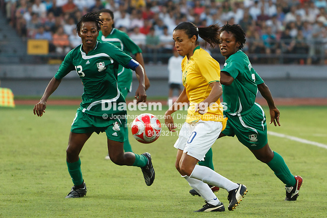 BEIJING, CHINA - AUGUST 12:  Marta of Brazil (c) drives the ball against Nigeria defenders Christie George (l) and Stella Mbachu (r) during a Beijing Olympic Games women's soccer tournament match August 12, 2008 at Workers' Stadium in Beijing, China.  Editorial use only.  (Photograph by Jonathan Larsen)