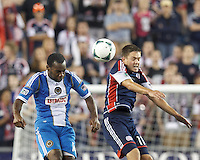 Philadelphia Union midfielder Amobi Okugo (14) and New England Revolution midfielder Kelyn Rowe (11) battle for head ball.  In a Major League Soccer (MLS) match, the New England Revolution (dark blue) defeated Philadelphia Union (light blue), 5-1, at Gillette Stadium on August 25, 2013.