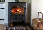 Roaring flames and warm glow of home multi-fuel stove fire burning wood and coal, UK