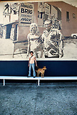 USA, Los Angeles, a woman standing in front of a wall mural on the side of a building on Abbot Kinney Boulevard with her dog