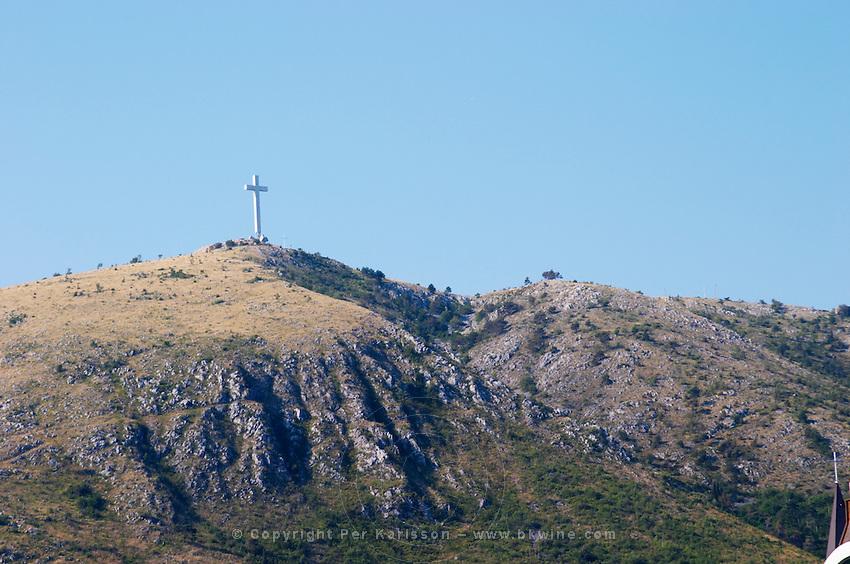 A cross on a hilltop near the city. Historic town of Mostar. Federation Bosne i Hercegovine. Bosnia Herzegovina, Europe.