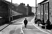 An elderly man walks down the middle of the deserted main road through Rookhope, an ex-mining villlage in County Durham. The village once had eight shops; it now has one, which doubles as a part-time post office.