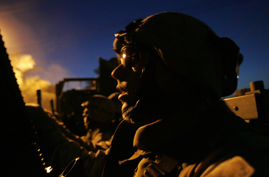 Marines with 1st Platoon Golf Company 2nd Battalion 5th Marines hunkered down behind the homemade armor of a 7-ton truck return from a patrol that led to the discovery of a stash of weapons hidden by insurgents in an abandoned amusement park in central Ramadi on January 7, 2005.