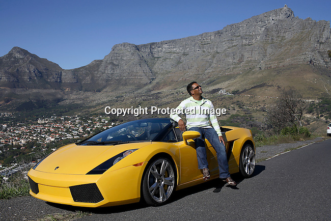 Raghavan Moonsamay, a newly rich man poses with his yellow Lamborghini. He collects cars and properties. He has a red Ferrari, An Aston Martin, a few Mercedes, several high-end properties in Cape Town.  Photo by: Per-Anders Pettersson/Getty Images for Smithsonian Magazine.