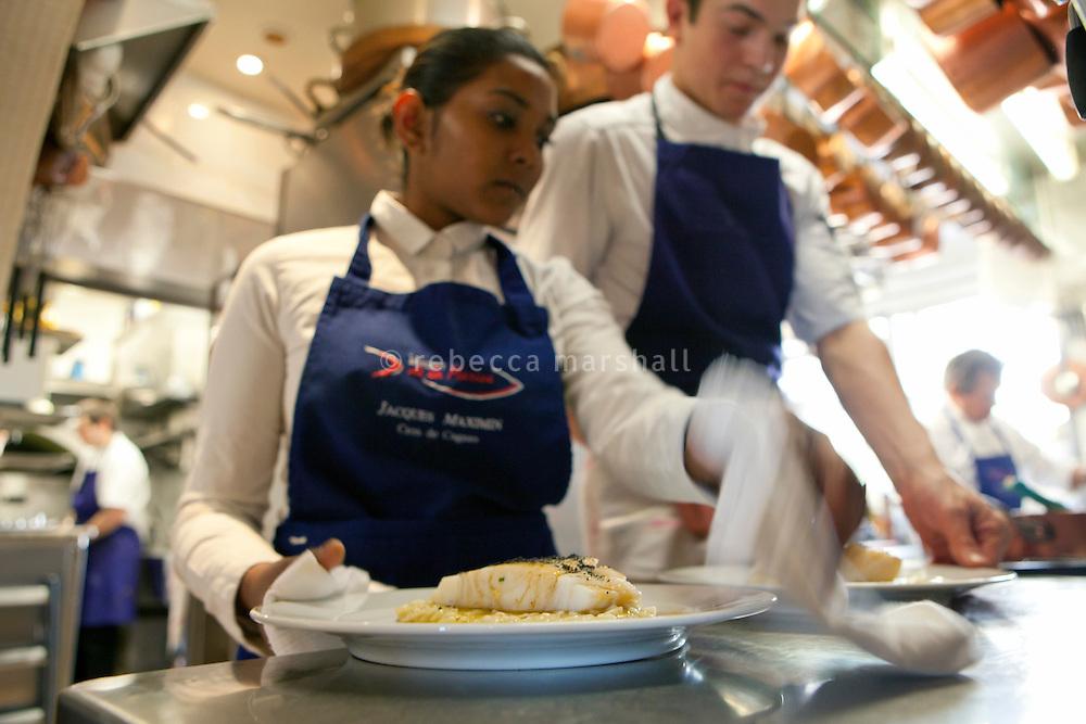A waitress collects a dish from the kitchen at Jacques Maximin's restaurant Le Bistro de la Marine, Cagnes sur Mer, France, 07 April 2012