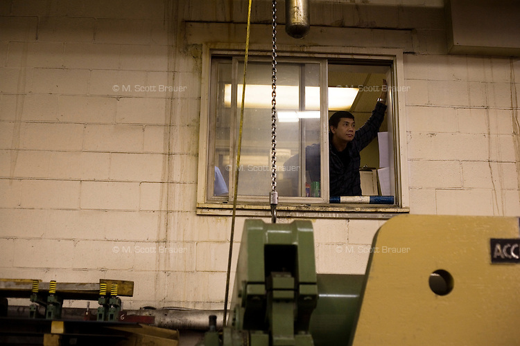 An employee watches a Romney campaign event to begin at Gilchrist Metal Fabricating in Hudson, New Hampshire, on Jan. 9, 2012.  Romney is seeking the 2012 Republican presidential nomination.