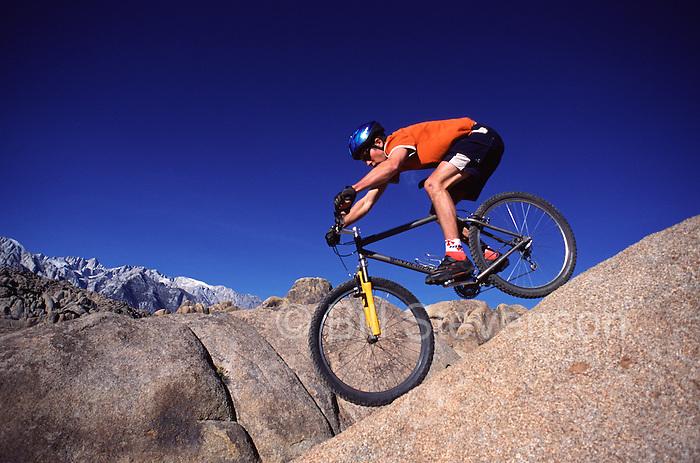 A photo of a man riding a mountain bike down a steep rock near Mount Whitney, CA.