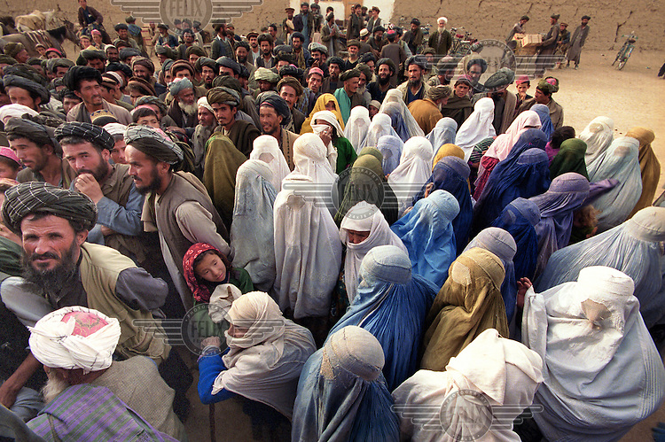 © Martin Adler / Panos Pictures..Northern Afghanistan. October 2001...Queueing up for food distribution in Nawabad refugee camp. The women, almost all still wearing the burqa, stand separately from the men.