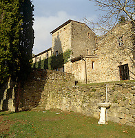 The ancient mellow stone walls of a villa in Tuscany seen from the lawns below