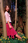 A912N6 Young girl leaning against a tree in daffodil woods