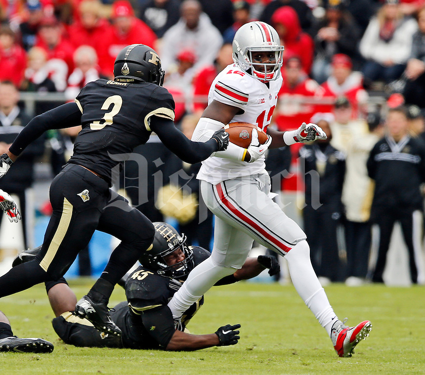 Ohio State Buckeyes quarterback Cardale Jones (12) runs upfield past Purdue Boilermakers linebacker Will Lucas (45) and defensive back Leroy Clark (3) during the fourth quarter of the NCAA football game at Ross-Ade Stadium in West Lafayette, Ind. on Nov. 2, 2013. (Adam Cairns / The Columbus Dispatch)