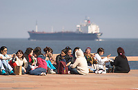 A group of young school children teenagers youth sitting on the pavement talking and drinking mate herbal tea, in the background a big freight ship on the river, along the river riverside coast walk Rio de la Plata Ramblas Sur, Gran Bretagna and Republica Argentina Montevideo, Uruguay, South America