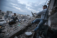 In this Sunday, Dec. 09, 2012 photo, Syrians residents collect combustible due the lack of suppleness at the top of a house buiding destroyed by aircraft in an area controlled by rebel fighters in the Tarik Al-Bab neighborhood of Aleppo, Syria. (AP Photo/Narciso Contreras)