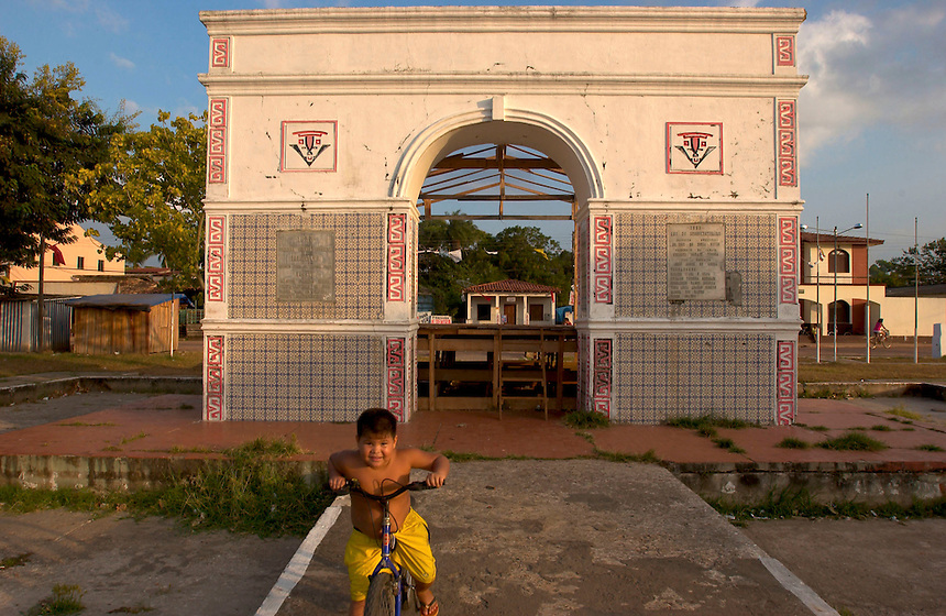 A young cyclist passes commemorative arch in the town of Cachoeira do Arari (acute accent on final i) on the island of Marajo (acute accent on the final o). The size of Switzerland, Marajo is a vast expanse of wilderness and cattle and water buffalo ranches, offering a close look at rural life in equatorial Brazil. (Kevin Moloney for the New York Times)