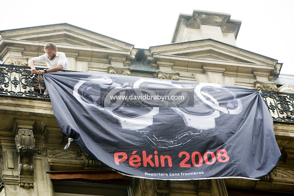 A man unfurls a banner during a street protest called by press watchdog Reporters Sans Frontieres against China's human rights policy close to the Chinese embassy in Paris, France, on the day of the inaugural ceremony of the 2008 Olympic Games in Beijing, 8 August 2008.
