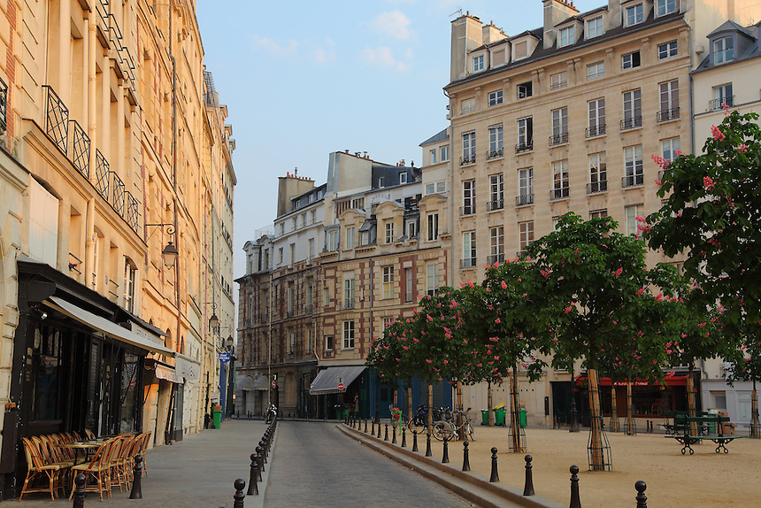 A lateral view of Place Dauphine in Paris with its triangular garden, the typical buildings, the trees and the benches, with a Parisian café in foreground. Digitally Improved Photo.