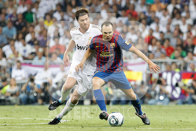 Real Madrid's Xabi Alonso (l) and FC Barcelona's Andres Iniesta during Spanish Supercup 1st match.August 14,2011. (ALTERPHOTOS/Acero)