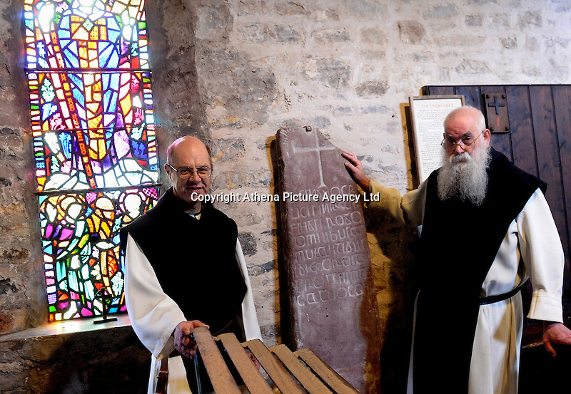 Pictured: Monks with the Ogham stone in the monastery on Caldey Island off the Pembrokeshire coast, Wales, UK. Circa 2006 <br /> Re: A small island off the Welsh coast known for its order of perfume-making monks and sense of tranquility has recorded its first crime in recent history.<br /> Police were called to Caldey Island which has apopulation of 40, off Tenby in Pembrokeshire, west Wales after an incident at the chocolate factory.<br /> The officers were taken on an RNLI lifeboat to the island, 2 miles off the resort of Tenby, to make an arrest.<br /> The crime was revealed when a visitor from Dudley, West Midlands, appeared in Haverfordwest magistrates court and admitted assault. The man was visiting the island when he struck his  7 year old son during a visit to the chocolate factory, where handmade treats are produced by monks.