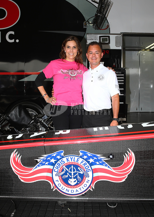 Apr 24, 2015; Baytown, TX, USA; NHRA top fuel driver Steve Torrence (right) poses for a photo with Taya Kyle , wife of US Navy sniper Chris Kyle in the pits during qualifying for the Spring Nationals at Royal Purple Raceway. Torrence announced a partnership with the Chris Kyle Frog Foundation. Mandatory Credit: Mark J. Rebilas-