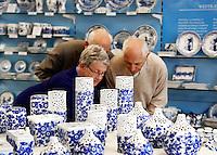 Delft- De Porceleyne Fles. Fabriek waar delftsblauw aardewerk wordt vervaardigd. Er is tevens een museum gevestigd. Mensen bekijken aandachtig de producten in de souvenirwinkel