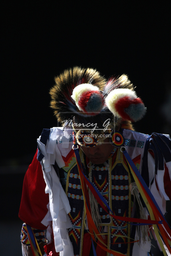 A Native American Indian man dancing in a fancy outfit looking down at a Pow Wow at the Milwaukee Lakefront Indian Summer Festival, Wisconsin