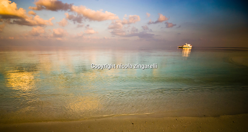 Maldive Islands, Indian Ocean. Mother vessel moored inside a laggon at sunset with calm water and beautiful colors