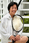 Asian woman holding tennis racket, smiling