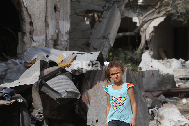 A Palestinian girl stands on the rubble of the destroyed houses and buildings that were destroyed during the devastating 50-day war between Israel and Hamas at Al-Shojae'ya neighborhood east of Gaza City on October 11, 2014. ahead of a donors conference in Cairo aimed at gathering efforts to the reconstruction of the Gaza Strip after the devastating 50-day war between Israel and the Hamas militants who run the coastal Palestinian enclave. The Palestinian government has unveiled a 76-page reconstruction plan for Gaza, calling for $4 billion to rebuild the war-battered territory, with the largest amount going to build housing for some 100,000 left homeless. Photo by Mohammed Asad