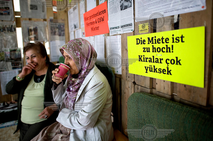 Poster reading Die Miete ist zu Hoch, Kiralar cok yueksek..Turkish and German women inside their protest camp at Kottbusser Tor in Kreuzberg in Berlin. The protesters are demonstrating against rising rents, the change of the social structure and social dispacement in Berlin, especially in Kreuzberg's Kottbusser Tor, Kotti, neighbourhood. Symptom of a steady process of gentrification which is rapidly forcing poorer residents out of the city centre and tearing apart the city's social fabric.