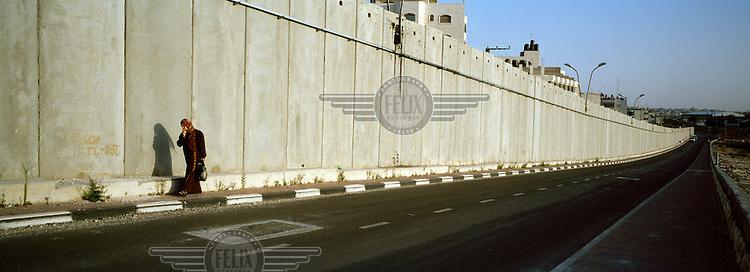 A Palestinian woman walking alongside the Israeli separation wall / barrier.