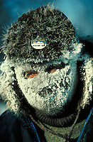 Close-up of a musher (dog sled driver) in the Anchorage-to-Nome Iditarod race, face mask is covered with ice. protective clothing, hat. Alaska Iditarod Trail.