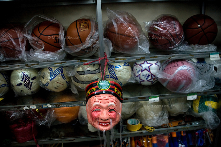 A mask made to look like an old Chinese man hangs on shelves holding basketballs, soccer balls, and other sporting equipment, in Haikou, Hainan, China.