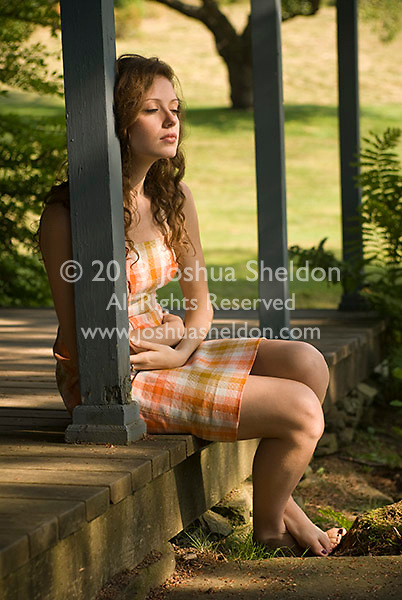 Young woman sitting on porch barefoot, eyes closed