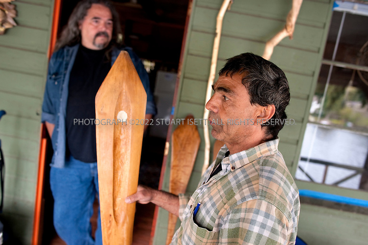 "5/7/2009--Sammamish, WA, USA..John Mullen (right), employed as the Snoqualmie tribe's master carver holding a paddle he carved, stands with his brother, Ray Mullen (left) at John's cabin on Beaver Lake in Sammamish...The Snoqualmies--who once dominated Western Washington, controlling the all-important trade route through the Cascades to the sea-- wasn't even recognized by the federal government and had no reservation or land of its own. Their quest for government recognition took decades--years in which they pieced together enough evidence of cohesion to convince the U.S. Bureau of Indian Affairs (BIA) to recognize them as a ""domestic sovereign nation"" under federal law--a designation they had lost in 1952 (see sidebar). When they were finally granted this status in 1999, the tribe embarked on a quest to makes its dreams--a reservation that tribal members could call home, world-class health care for Snoqualmies and other Northwest natives, and access to as much education as any individual tribal members would want to pursue--come true...©2009 Stuart Isett. All rights reserved."
