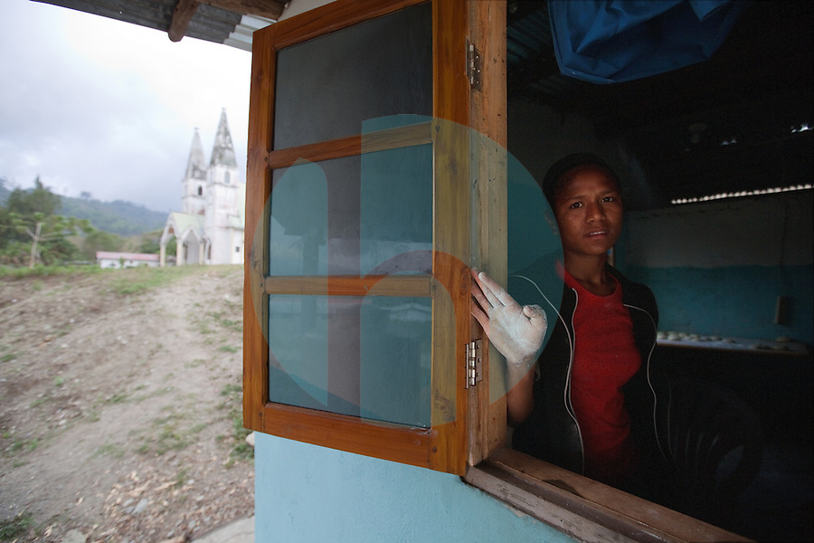 With the town's main church in the background, a young girl looks out the window of a bakery in the mountain town of Laclubar, Timor-Leste on Tuesday, Oct. 18th, 2011.  Photographer: Daniel J. Groshong/The Hummingfish Foundation