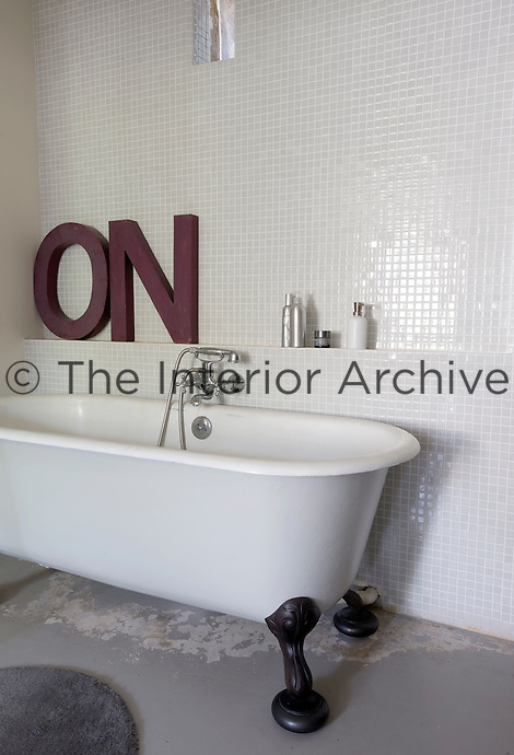 """""""On"""" is spelt out in letters on the ledge above the roll-topped bath in this mosaic-tiled bathroom"""