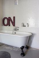 """On"" is spelt out in letters on the ledge above the roll-topped bath in this mosaic-tiled bathroom"