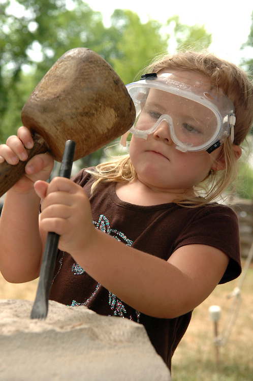 Ella DuCharme, 11, of Texas, chisels Indiana limestone at the stone masonry exhibit at the Smithsonian Folklife Festival.