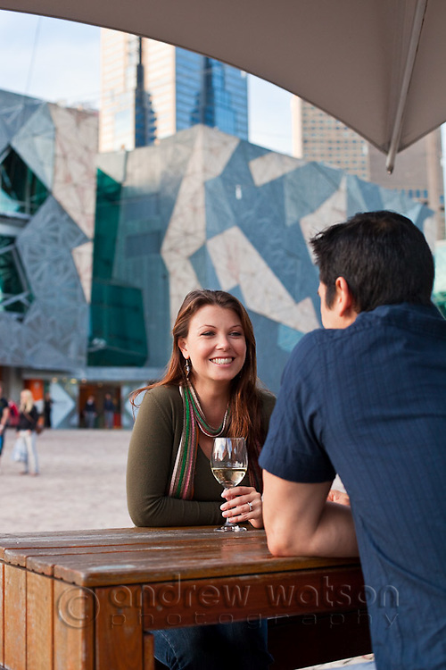 Young couple enjoying drink at an outdoor bar.  Federation Square, Melbourne, Victoria, Australia