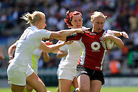 Mandy Marchak of Canada breaks through the tackle of Michaela Staniford (left) and Joanne Watmore of England during the iRB Marriott London Sevens at Twickenham on Sunday 13th May 2012 (Photo by Rob Munro)