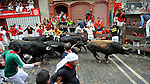 People run in front of Jandilla´s fighting bulls during the fifth bull run in the San Fermin Festival on July 11, 2014, in Pamplona, Basque Country. Every year, tens of thousands of people pack Pamplona's streets for a drunken kick-off to one os worls's best-known fiesta: the nine-day San Fermin bull-running festival. (Ander Gillenea / Bostok Photo)