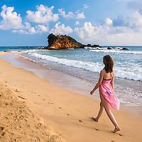 Tourist walking along Mirissa Beach, South Coast of Sri Lanka, Southern Province, Asia. This is a photo of a tourist walking along Mirissa Beach, Sri Lanka, Asia. Mirissa Beach is a popular sandy tourist beach on the South Coast of Sri Lanka.