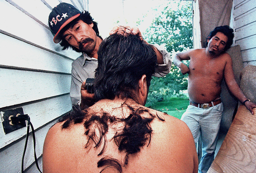 Manuel cuts hair for a housemate in Pittsboro while Erasmo waits his turn.