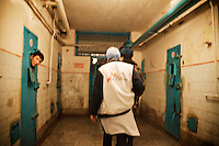 A prisoner sticks his head out of his cell as MSF (Medecins Sans Frontieres) staff walk down the corridor where tuberculosis (TB) patients are detained in SIZO 1, a pre-trial detention centre. Kyrgyzstan's prisons are experiencing a TB epidemic, where the incidence rate is estimated at 25 times higher than in civil society.