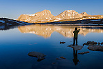 Sunrise fly fishing at French Lake with the reflections of Merriam peak, Royce peak and Feather Peak in the High Sierra mountains near French Canyon and Pine Creek Pass.